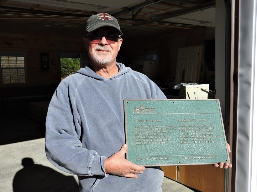 Peter Lohnes with National Historic Site Plaque for his home Mount Hope Farm, Westfield, N.B