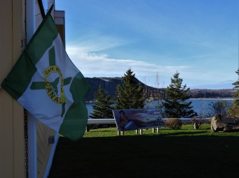 Cape Breton Flag on Tourist building Intrepretive sign posts and Porcinpine mountain in background