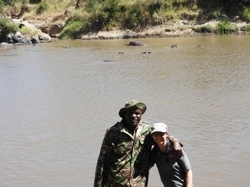Me with Ranger at bank of Mara River hippos in water behind us