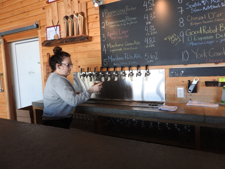 Ashley pouring a pint at Grimross craft brewery